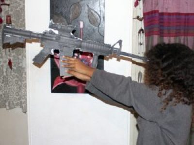 "Toveet's sister ""M"" holds a model of Toveet's rifle to her head with one hand, as the IDF report posits Toveet did, and fails to reach the rifle's trigger with her other hand. – Photo: David Sheen"