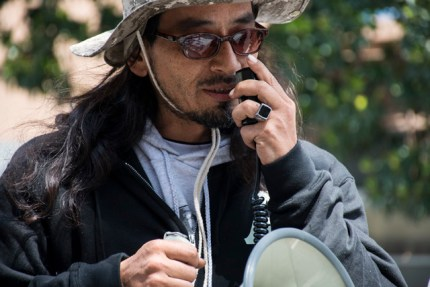 Ilych Sato, the rapper known as Equipto, speaking on Day 5 of the hunger strike, is the son of KPFA jazz host Art Sato and teacher Maria Cristina Gutierrez, who initiated the hunger strike. – Photo: Lola M. Chavez, Mission Local