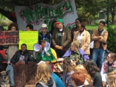 "At their huge May 9 rally, TWELF 2016 hunger striker Ahkeel Mestayer read their demands, concluding with the statement: ""We are the Third World Liberation Front, the campaign to defend and advance ethnic studies and the historical organizations at San Francisco State University!"" That's Hassani Bell seated to the left of Ahkeel. – Photo: Steve Zeltzer, Labor Video Project"