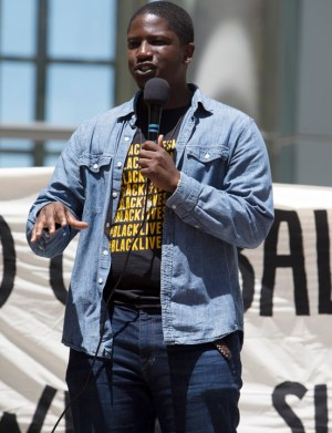 Devonte Jackson, Bay Area organizer for the Black Alliance for Just Immigration and Black Lives Matter, Bay Area Chapter, speaks during two hours of picketing in front of the Oakland Federal Building on the Day of Action for Haiti. – Photo: Malaika H Kambon