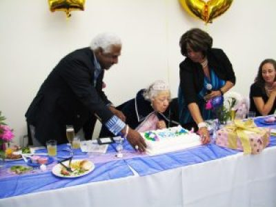 Ms. Pickens blows out the candles on her 100th birthday cake at the Senior Center in celebration of a long life well lived. – Photo: Anh Le