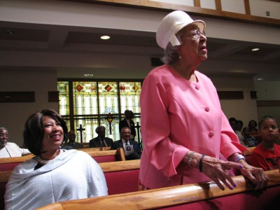 Ms. Verlie Mae Pickens stands tall at the celebration of her 100th birthday following Sunday services at Jones Memorial United Methodist Church on June 12, as her granddaughter, Charisse Anderson, looks on. – Photo: Anh Le