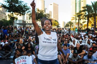 Ethiopian-Israeli activist Inbar Bugala gestures while a crowd of mostly Ethiopian-Israeli protesters sits in the roadway, blocking vehicular traffic. – Photo: Benny Woodoo