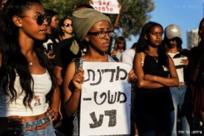 """An Ethiopian-Israeli protestor holds a sign that reads: """"[Evil] police state."""" – Photo: Benny Woodoo"""