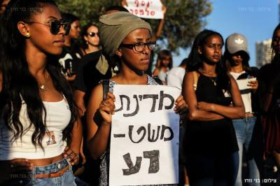 "An Ethiopian-Israeli protestor holds a sign that reads: ""[Evil] police state."" – Photo: Benny Woodoo"