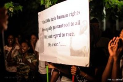 """Ethiopian-Israeli protestors hold aloft a sign bearing the images of Yosef Salamsa and Avera Mengistu and a quote from the song """"War"""" by Bob Marley and the Wailers. – Photo: Benny Woodoo"""