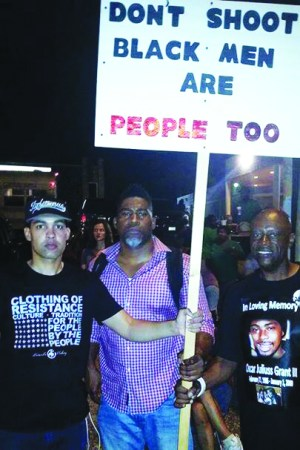 "Uncle Bobby joins the nightly protests in Ferguson on Aug. 24, 2014, with Jasiri X and David Banner. Their sign's message, ""Black men are people too,"" suggests the phrase ""Black Lives Matter,"" which hadn't yet caught on but soon became the rallying cry for the movement to end police terror."