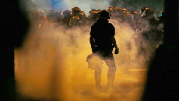 """The caption for this photo written by The Associated Press describes police-initiated violence: """"Police fire teargas as protestors converge on downtown following Tuesday's police shooting of Keith Lamont Scott in Charlotte, N.C., Wednesday, Sept. 21, 2016. Protesters have rushed police in riot gear at a downtown Charlotte hotel and officers have fired tear gas to disperse the crowd. At least one person was injured in the confrontation, though it wasn't immediately clear how. Firefighters rushed in to pull the man to a waiting ambulance."""" – Photo: Gerry Broome, AP"""