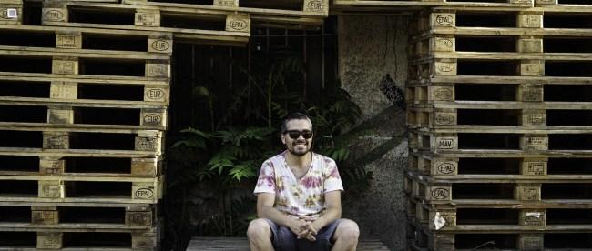Sebastián Godoy - Don Pallets sentado en un pallets y rodeado por una pila de pallets