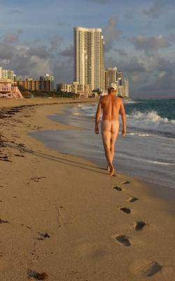 Man walking at sunrise on Haulover Beach