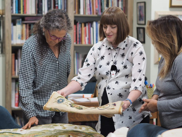2019 - Mae teaching crewelwork; showing pieces from the collection