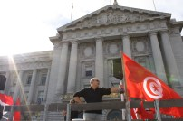 Eyad Kishawi stands next to the Tunisian flag on a flatbed truck carrying pro-Egypt revolution demonstrators as they cruise past San Francisco City Hall Feb. 5, 2011. (Alex Emslie)
