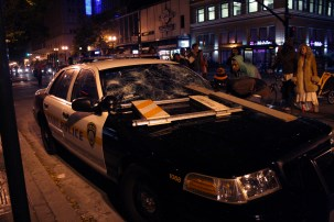 It took about 20 seconds for a handful of people to destroy this empty BART Police car parked near 12th and Broadway during a July 13, 2013, march in Oakland protesting the acquittal of George Zimmerman for killing unarmed black teenager Trayvon Martin last year in Florida. (Alex Emslie/KQED)