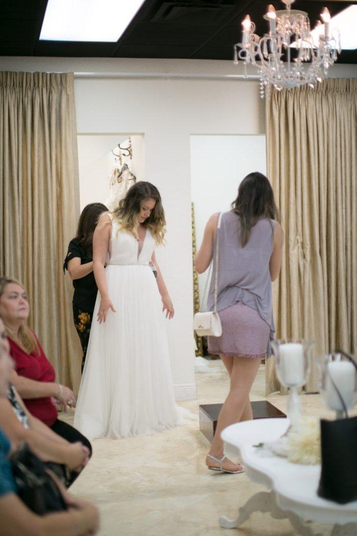 Braut, die auf Brautkleidern versucht, während Hochzeitskleid für ein Maggie Sottero Brautkleid einkauft