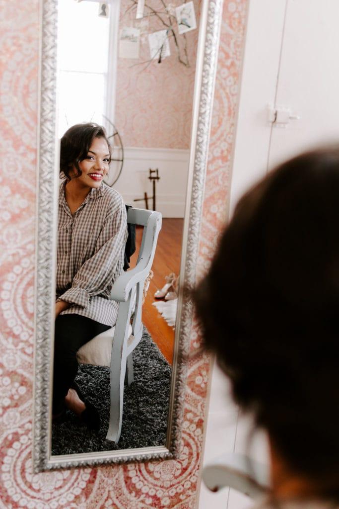 Braut, die im Spiegel schaut und Hochzeits-Make-up trägt