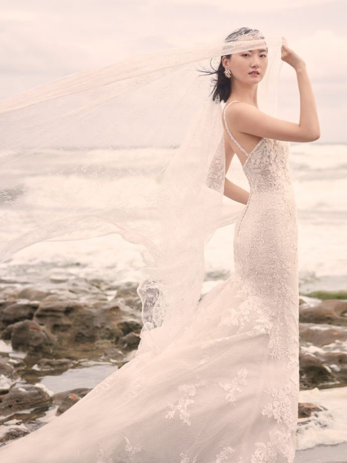 Model on Beach Wearing Lace Mermaid Wedding Dress with Long Train Called Bryan by Sottero and Midgley