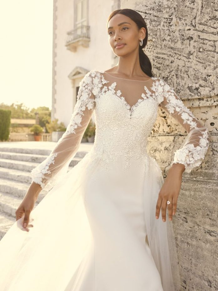 Bride wears a 3-D wedding dress with floral lace and bishop sleeves, called Arta by Sottero and Midgley
