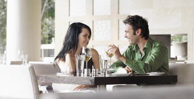 Couple Talking Over Wine At Restaurant