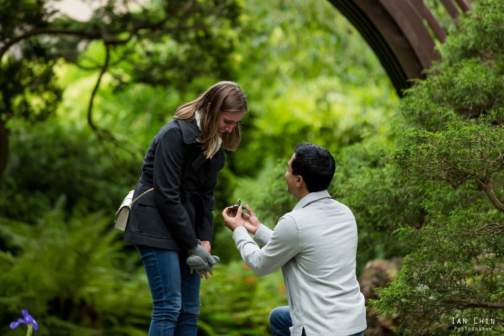 Japanese Tea Garden marriage proposal with a guy on his knee holding out a ring to a girl with gray gloves looking at the ring crying