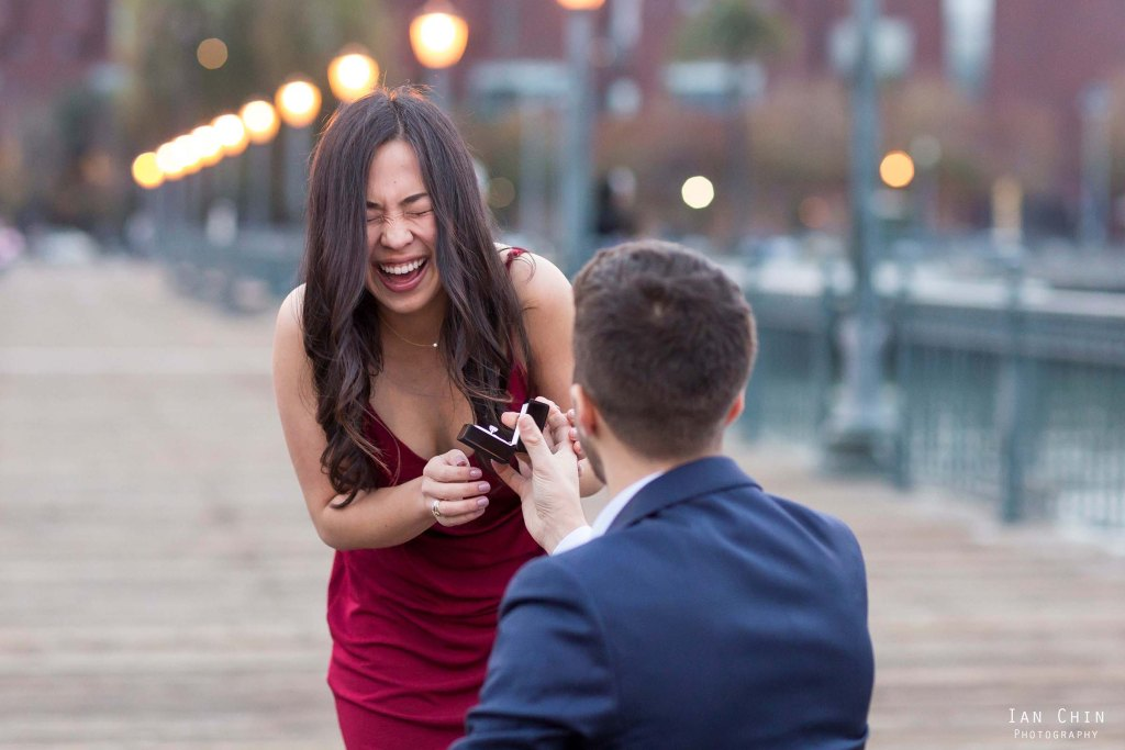 girl laughing during a marriage proposal at pier 7 in san francisco while a guy in a blue suit proposes on his knee