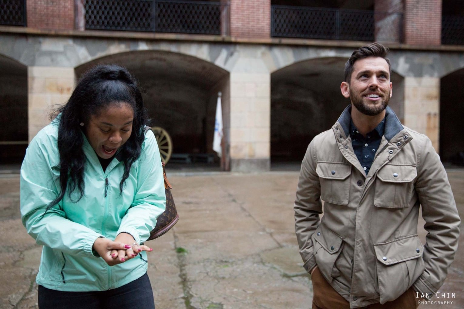 fort point marriage proposal in san francisco girl looking at ring on her hand in a green jacket while her boyfriend stands there smiling