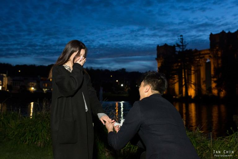 Palace of Fine Arts marriage proposal at night, with the guy on his knee and the girl covering her mouth in shock wearing black
