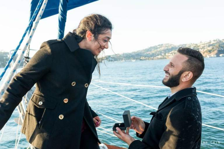boat marriage proposal with the guy on his knee in a black jacket and the girl smiling on a boat