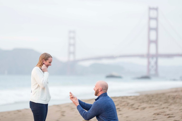 baker beach marriage proposal with the guy wearing a blue jacket on his knee proposing to his girlfriend with the golden gate bridge in the background