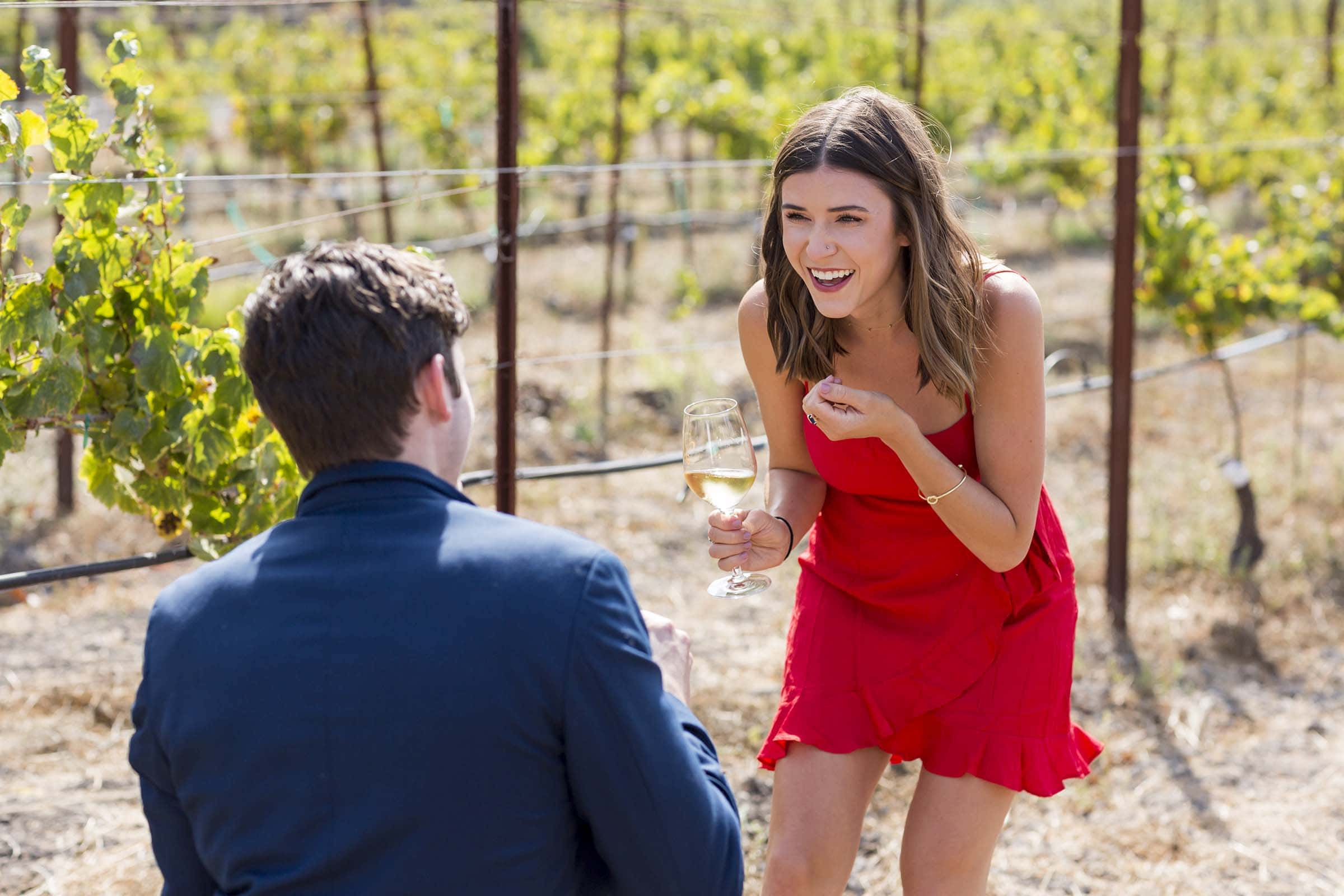 Cline Cellars marriage proposal in Napa girl in red dress smiling as guy in blue jacket is on his knee proposing