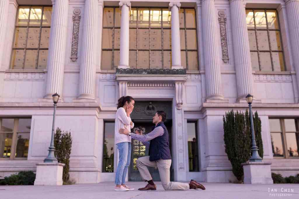 UC berkeley marriage proposal with the library in the background and the man on his knee wearing a black vest with the girl holding her mouth