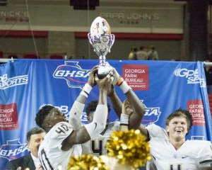 Colquitt QB Chase Parrish (4) holds the State Championship trophy with his teammates on the dais. Photo:Shine Rankin Jr. /SGSN