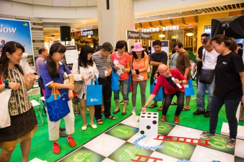 Emcee Lin Youfa demonstrating how to play the life-sized Snakes & Ladders financial game (1)
