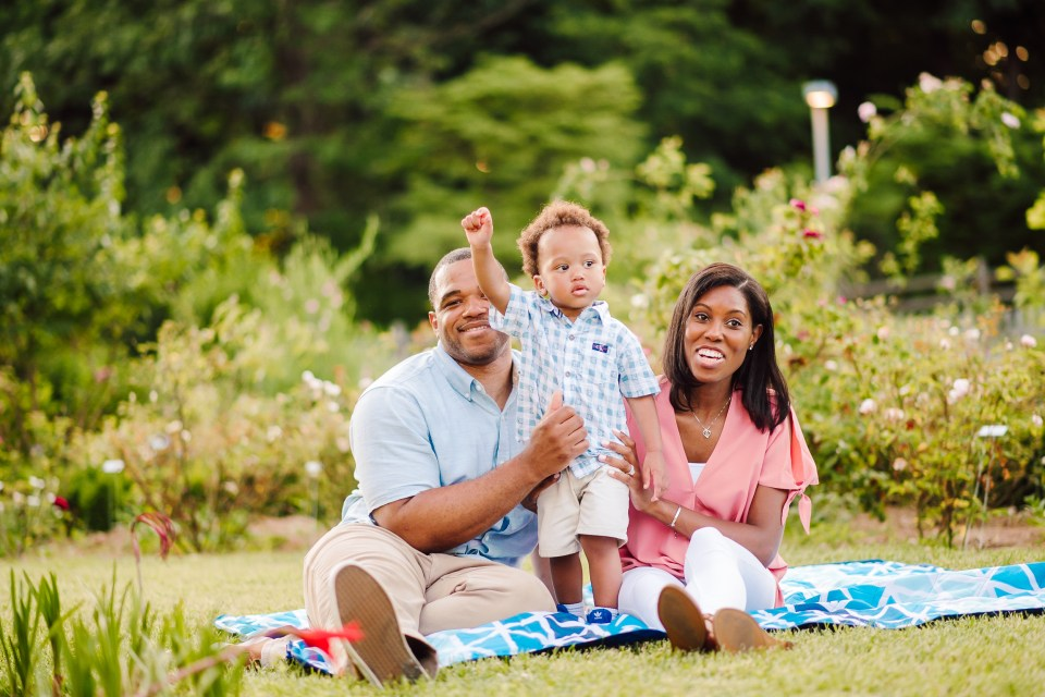 family sits in garden at bartram's