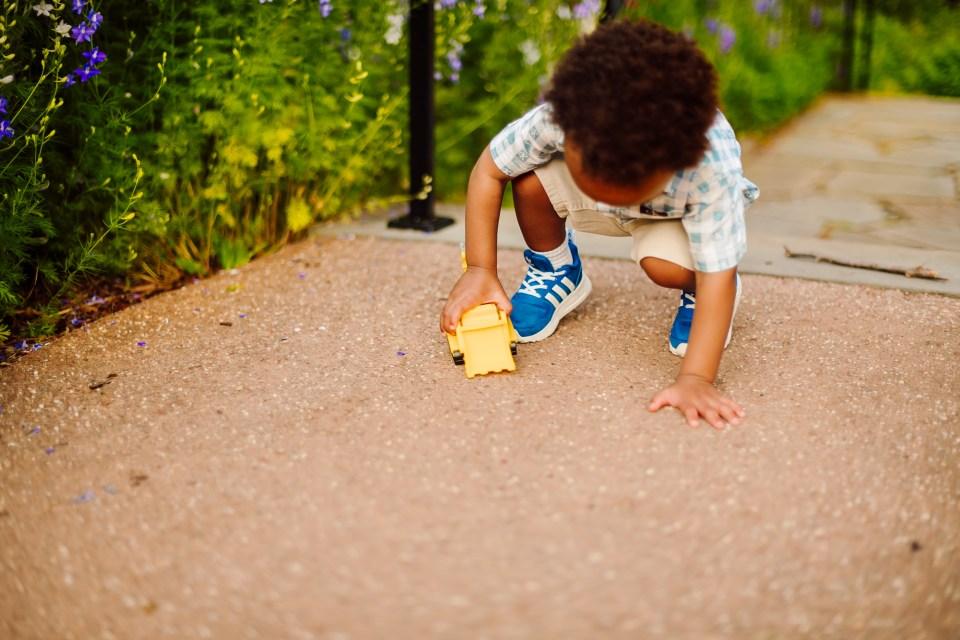 boy plays with toy truck in bartram's garden