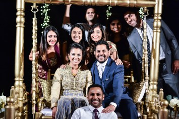 Bride and groom's friends posing for a photo at an Indian wedding reception.