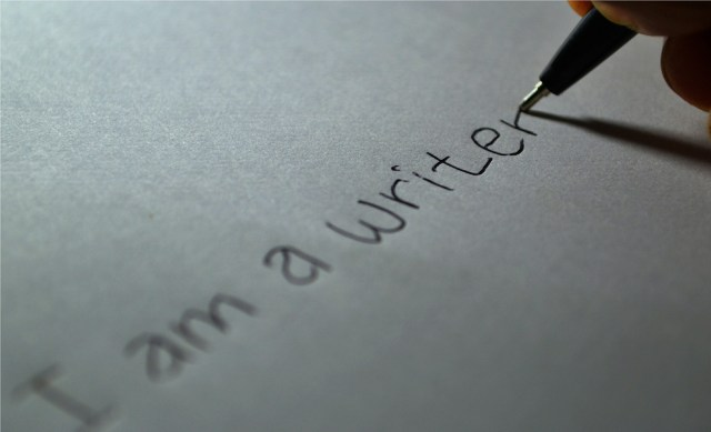 The words 'I am a writer' on a white piece of paper, a pen finishing off the last r.