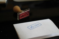 """File: An ink stamp in the shape of a Facebook """"LIKE"""" icon is used on a folded sheet of white paper. (Flickr / Denis Dervisevic)"""