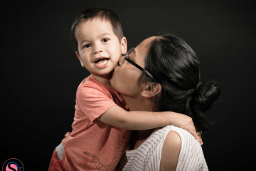 Woman kissing young boy on cheek against black background. An Aunt Writes