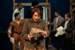 Viola (played by Chiara Motley) reads a letter. She is disguised as a man..