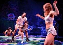 "Hermia (Melisa Soledad Pereyra) lunges at Helena (Cristina Panfilio). Lysander (Tyrone Phillips) attempts to restrain her as Puck (Sam Kebede) looks on with delight. ""A Midsummer Night's Dream,"" Chicago Shakespeare Theater. Photo by Liz Lauren."