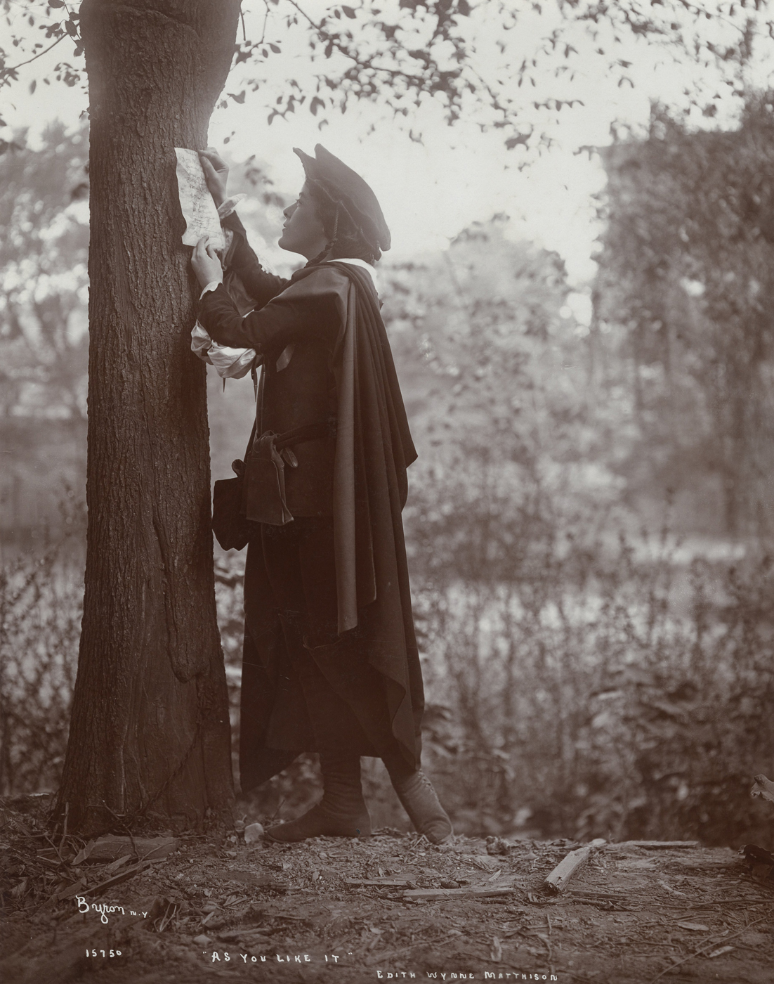 Black and white photo of a 1903 production of As You Like It. Rosalind, played by Edith Wynne Matheson, reads a poem pinned to a tree.