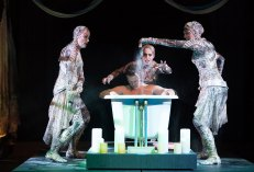 """Three witches surround Macbeth, seated in a bathtub, in """"Macbeth' at Oregon Shakespeare Festival"""