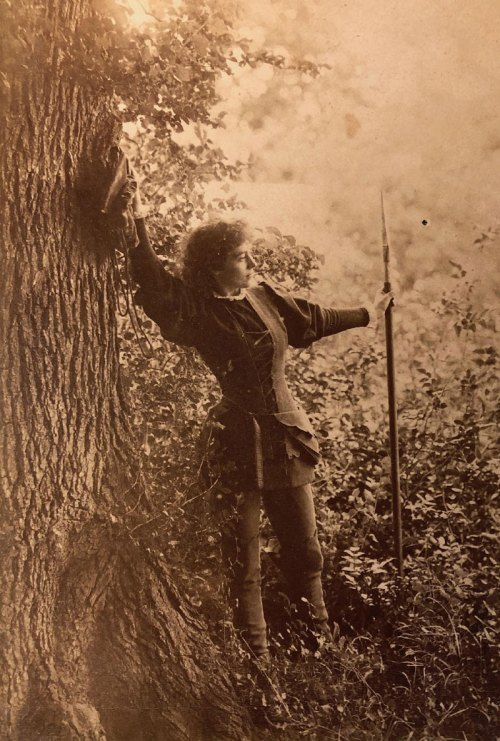 Photograph of a woman leaning against a tree