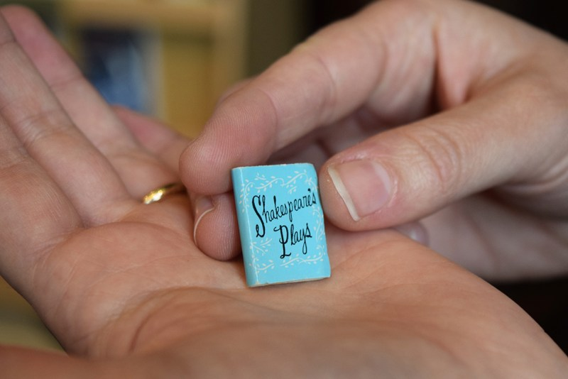 A tiny blue dollhouse book, titled Shakespeare's Plays, sitting in a person's hand.
