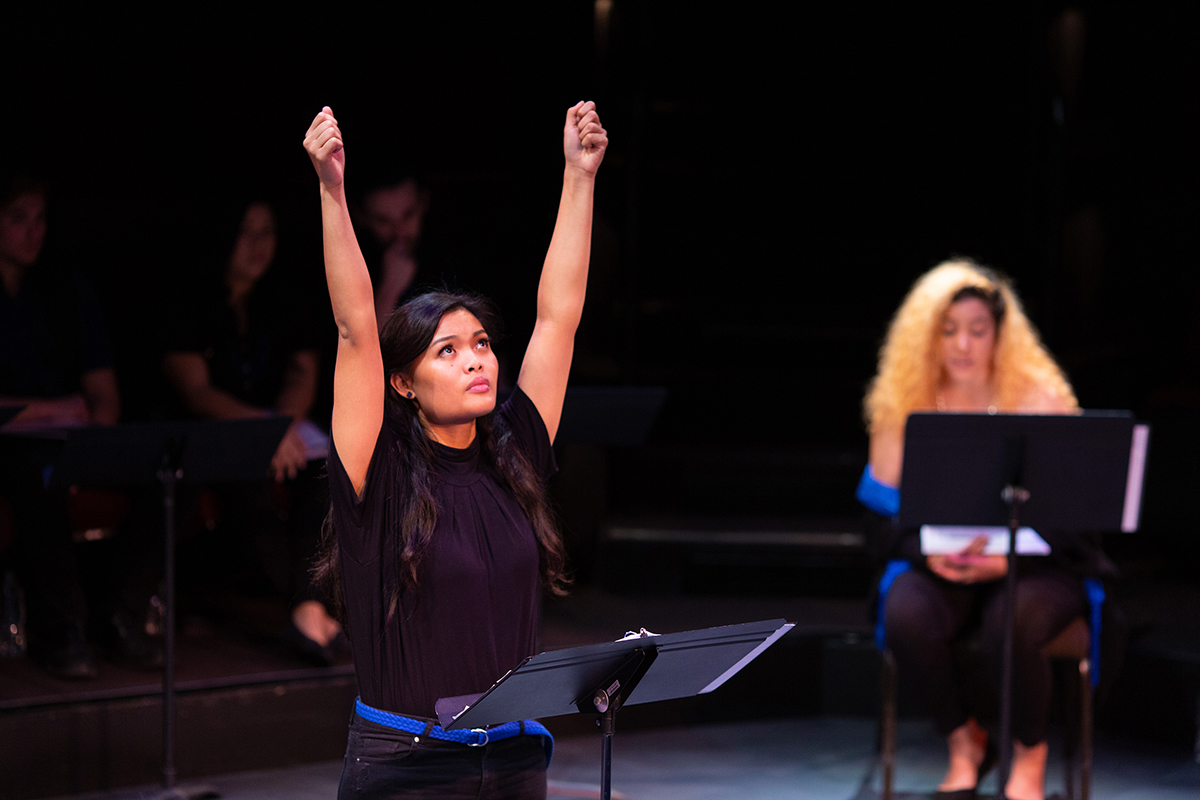A young woman with her arms stretched out above her, as if holding an imaginary sign in the air. Reanne Acasio and Anita D. perform in Celebrating Community Voices at the Powers New Voices Festival, 2019.