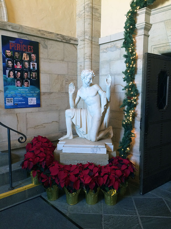 Puck statue surrounded by holiday greenery