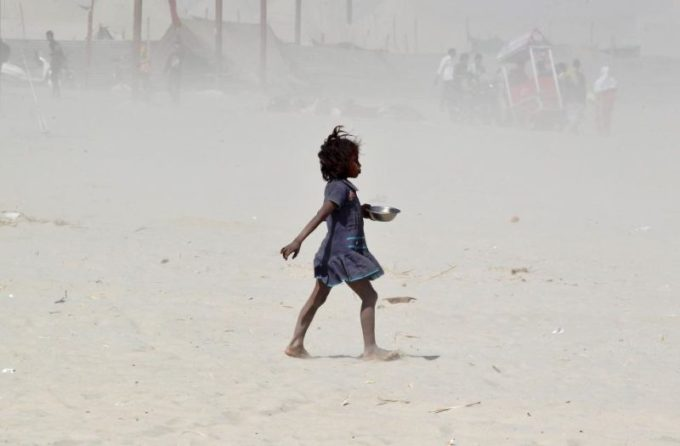 A girl walks amidst a dust storm on the banks of the Ganges river in Allahabad