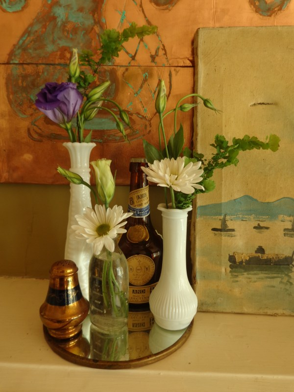 Mantel arrangement with milk glass vases, old bottles, purple lisianthus, shasta daisies, maidenhead fern from Fresh Flowers post on Shalavee.com