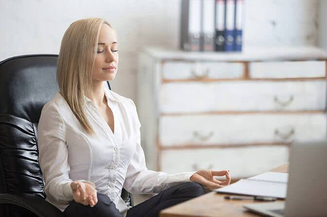 Business Woman Resting In Yoga Pose - 5 Ways to Lower Noise and Pressure in Your Office by Alex Charfen