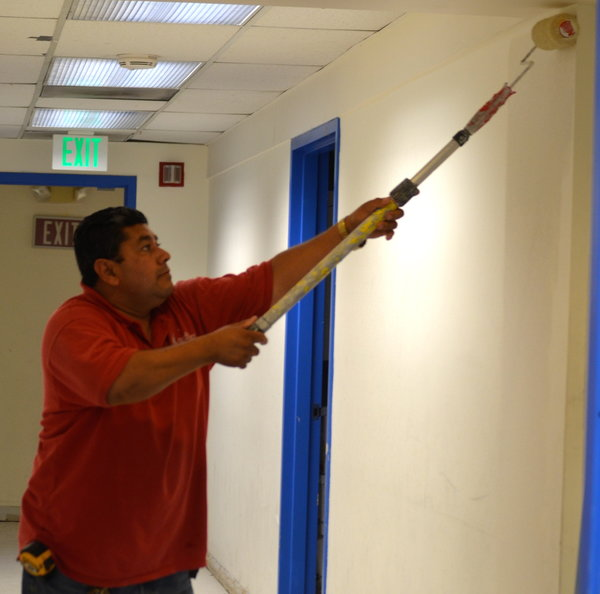 GETTING READY: Maintenance chief Jose Flores applied new paint to a hallway in the Annex.